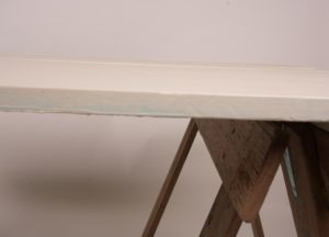 Cream trestle table top edge on brown timber trestle legs