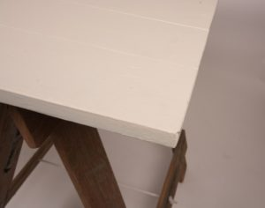 White cream trestle table top corner with brown timber trestle legs