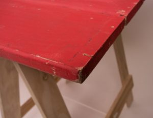 Red painted trestle table corner