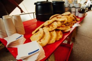 Red Trestle Table with naan bread, soups and coffee cups and mugs on top. Aria Catering napkins seen on table