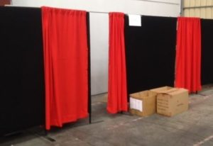 Change rooms with red curtains. Cardboard are in the front of one change room