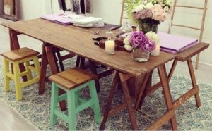 Rustic wooden trestle tables with flowers and candles on top. Vintage timber trestle legs are underneath with wooden stools on one side