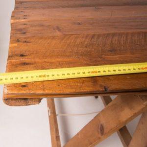 Vintage trestle table corner with tap measurer showing length