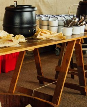 Vintage trestle table with soup pot, cups and bread on top of the table