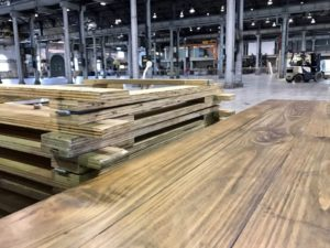 Reclaimed trestle tables with plywood trestle legs stacked next to the tops, inside of a large warehouse
