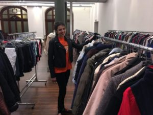 Woman standing near many chrome clothing racks. All have many items of clothing hanging off