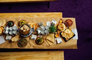 Wooden benches with a tray covered in brown paper with various foods on top