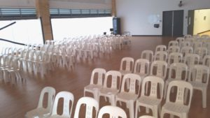Many white plastic stacking chairs lined up in rows inside building