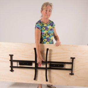 Woman holding plywood timber folding table with the legs folded in