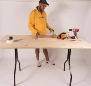 Man standing behind plywood timber folding table with various tools on surface