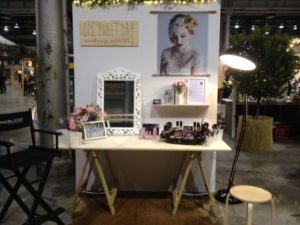 Traditional Plywood trestle table in front o a white backdrop with makeup and a mirror on top