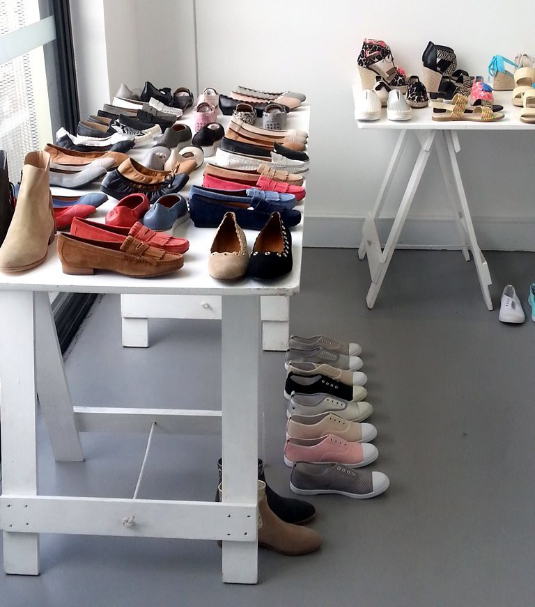 White painted trestle table with various shoes on top