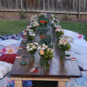 Boho picnic trestle table with flower bouquets in vases on hire