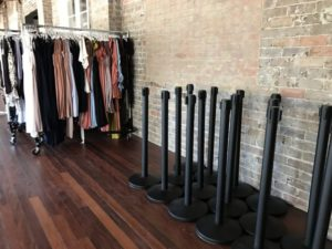 Black bollards with High Z racks in the background. Many clothes hang of the racks