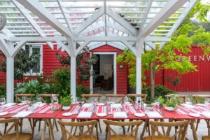Red painted trestle table outside under a white timber canopy. Wooden chairs are around the tables and plates and cutlery on the surface