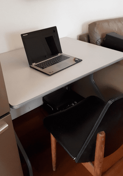 Small grey melamine folding table with a laptop on the surface and a chair in between the legs