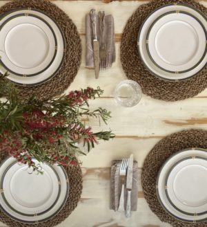 Washed pine timber trestle table with plates and cutlery on surface