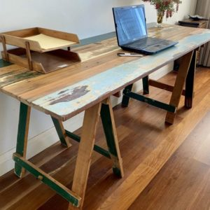 Reclaimed painted timber trestle table end with laptop and paper holder on surface