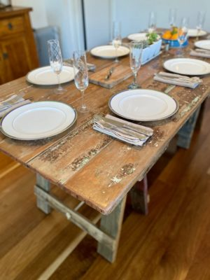 Wooden door trestle table corner with timber trestle legs and plates, cutlery and glasses on surface