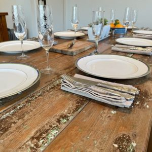 Wooden door trestle table with plates, cutlery and glasses on surface