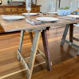Wooden door trestle table with timber trestle legs and plates, cutlery and glasses on surface