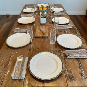 Reclaimed wooden door trestle table with plates, glasses and cutlery on top