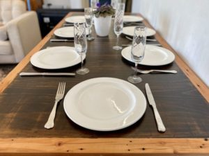 Stained Pine Table trestle table top with Oregon timber border on two black painted trestle legs. Plates, cutlery and glasses are on the surface