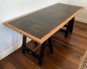 Stained Pine Table trestle table top with Oregon timber border on two black painted trestle legs