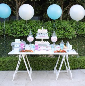 Hire White painted trestle table with white painted timber trestle legs. Various fruits and sweets are on the table top with four balloons hovering over and next top the table