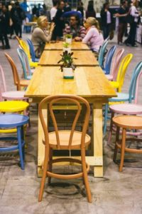 Wooden Trestle tables at Finders Keepers market Sydney. Couloured wooden chairs are on both sides of the tables with people in the background