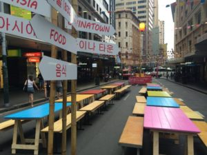 Various painted coloured wooden trestle tables outside in Syndey CBD. Wooden benches are on both sides of the tables with signs in both English and Chinese showing in the foreground