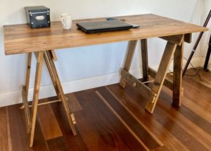 Reclaimed timber desk with laptop, mobile phone and pens on surface and reclaimed hardwood timber trestle legs