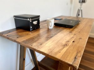 Reclaimed timber desk corner with laptop, mobile phone and pens on surface