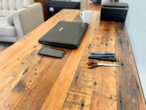 Reclaimed timber desk with laptop, mobile phone and pens on surface