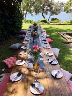 Boho Picnic tables used outside on grass near ocean. Plates, cutlery, wine glasses and candles are on the tables with cushions and rugs on either side
