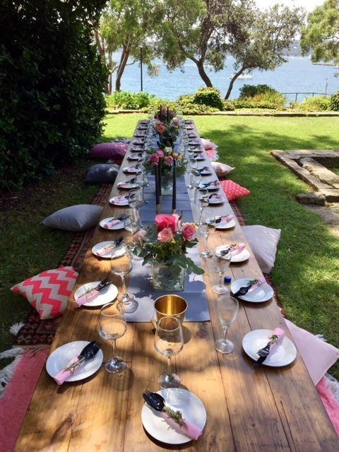 Boho Trestle Tables outside near the water with cushions on either side. Plates and flowers are top of the tables