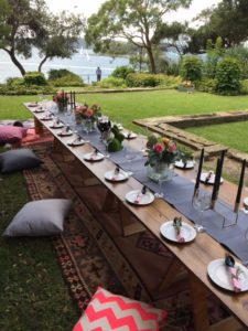 Low Boho trestle tables outide on grass with a view of the ocean in the background. The tables are on top of rugs with cushions on the sides and plates and glasses on top of the tables.