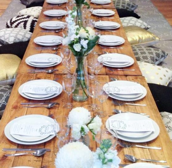 Reclaimed trestle tables on low boho legs with plates and cutlery. Cushions are around the sides of the table