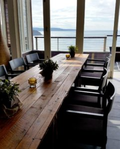 Vintage timber trestle table with black chairs on either side and a view of the ocean in the background