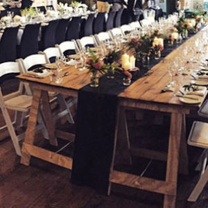 Reclaimed Trestle tables next to each other in a row to make an extra wide table. Chairs are on either side, with plates, cutlery, flowers and candles on the tables