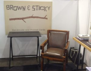 Black Exam table underneath sign for handmade greeting cards. Brown wooden chair is next to the table