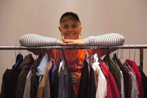Woan standing behind clothing racks with various jackets and shirts on rail