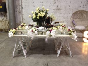 White painted trestle table with white painted trestle legs. The table is covered in flowers and glass cases with pieces of jewellery underneath