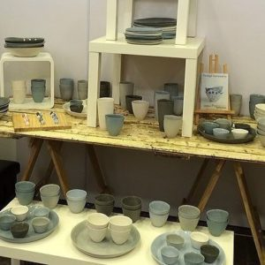 Wooden door trestle table with various types of ceramic bowls, plates and cups on top