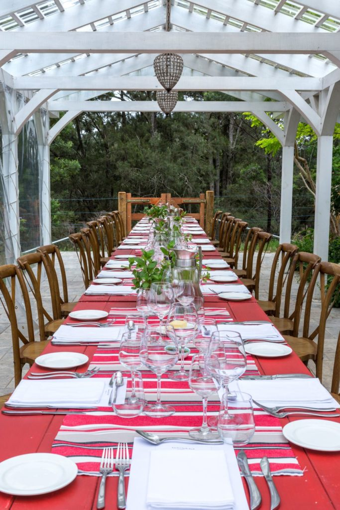 Red painted trestle tables line dup with white plates, napkins, cutlery, wine glasses and small pnats down the centre of the tables. Wooden chairs are on either side, underneath a white roof outisde